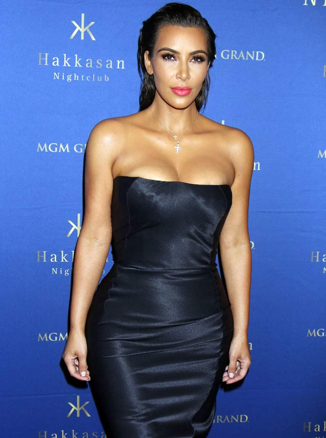 Kim with her hair pulled back in a sheer black satin dress