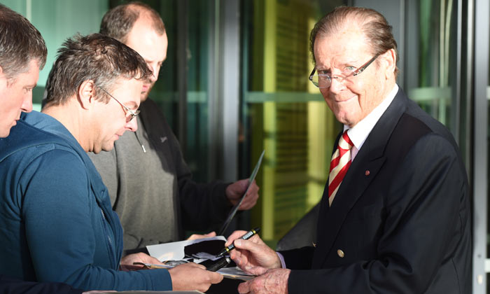 Ever the gent, Sir Roger Moore stops to sign autographs in 2015