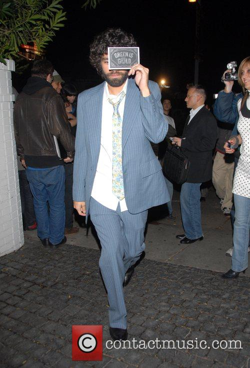 Adrian Grenier covers his face with a card...