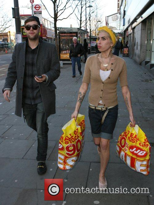 Amy Winehouse, Singer Friend Daniel Merriweather Indulge In Some Retail Therapy. Amy Spent Time Shopping In A Petrol Garage For Newspapers, A Sports Shop For Trainers, A Pharmacy For Make-up, A Fast Food Shop For Some Fried Chicken and Posing For Pictures With Fans Along The Way.