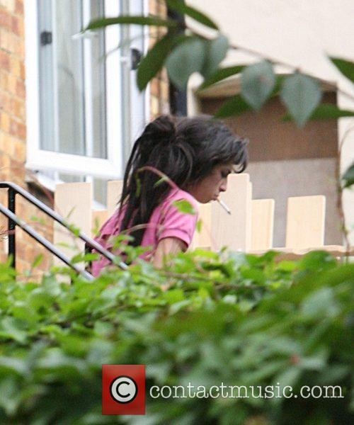 Amy Winehouse steps outside to smoke a cigarette...