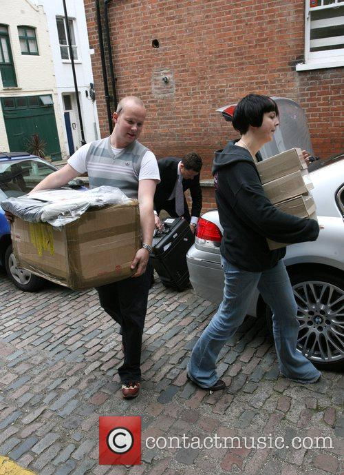 Amy Winehouse's tour manager outside carrying boxes to...