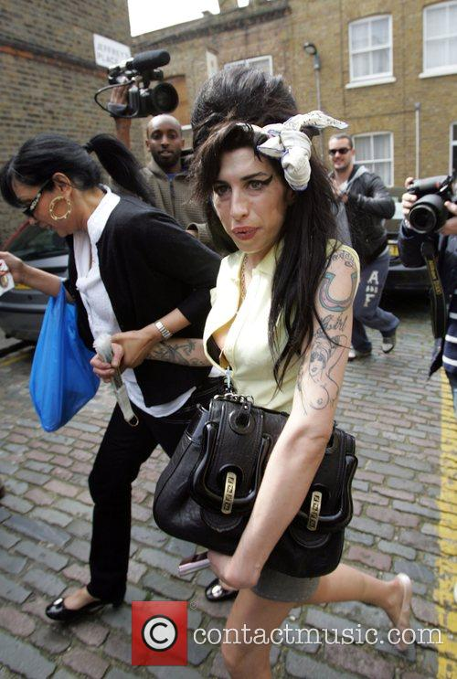 Amy Winehouse leaving her home this morning surrounded...