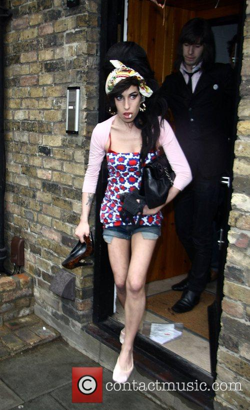 Amy Winehouse leaves home and waits outside for...
