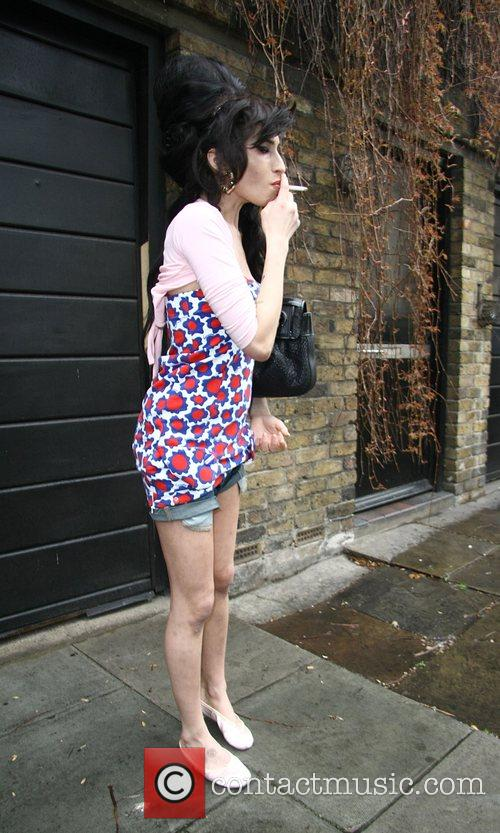 Amy Winehouse smokes a cigarette outside her home...
