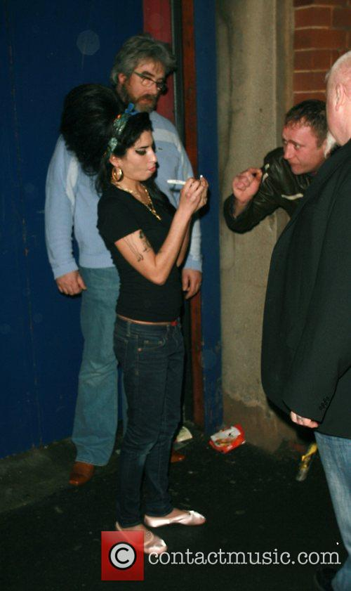 Amy Winehouse signing her autograph on a cigarette...