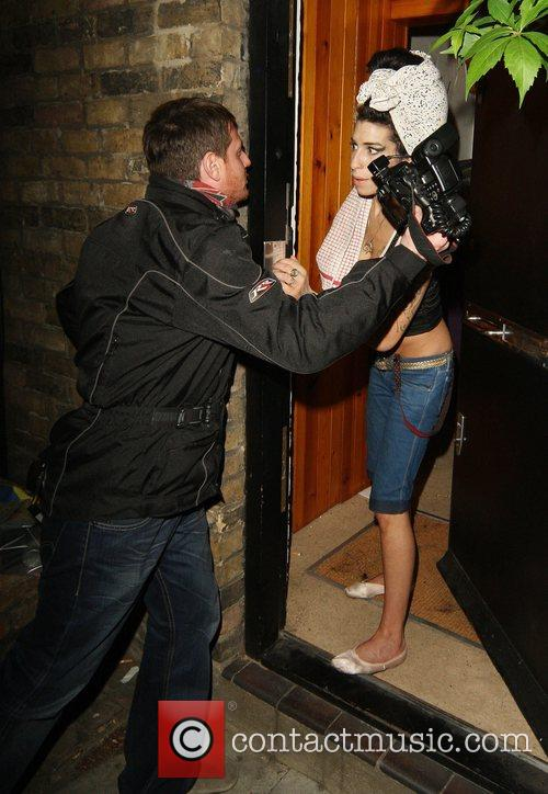Amy Winehouse  kisses a photographer outside her...
