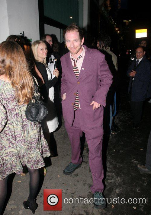 Comedian Paul Kaye posing in eye catching purple...