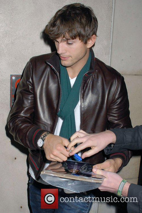 Ashton Kutcher signs autographs while arriving at his...