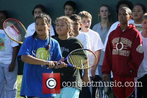 Young kids getting coached by some Pro tennis...