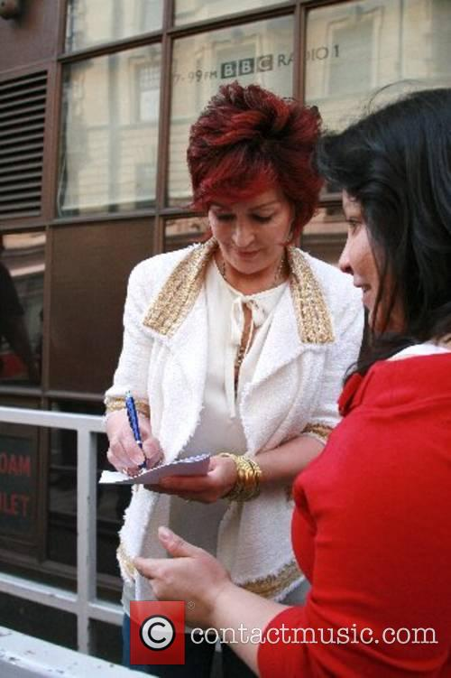 Sharon Osbourne signs autographs as she leaves the...