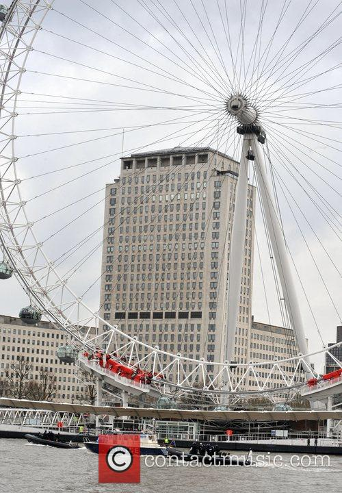 The Olympic Torch passes by the London Eye...