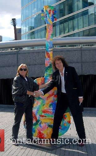 Brian May (R) signs a ten foot Gibson...