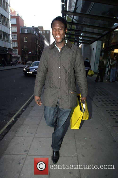 Leaving Selfridges department store with two shopping bags....