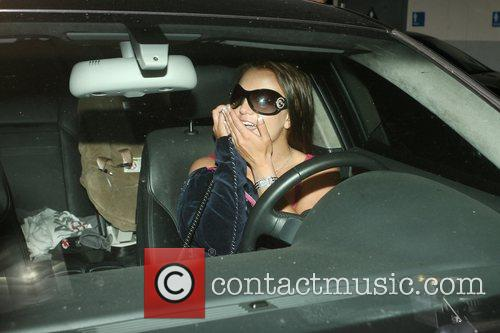 Britney Spears talks into her cellphone while stopping...