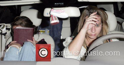 Britney Spears hides her face as she pulls...