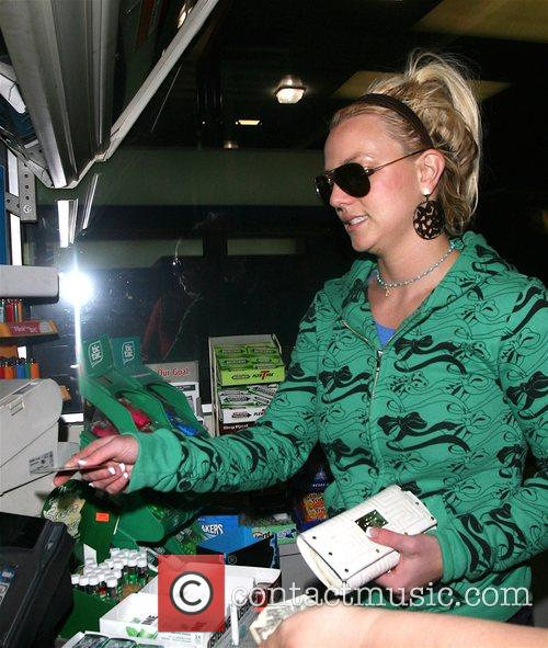 Britney Spears wearing green jacket and red boots,...