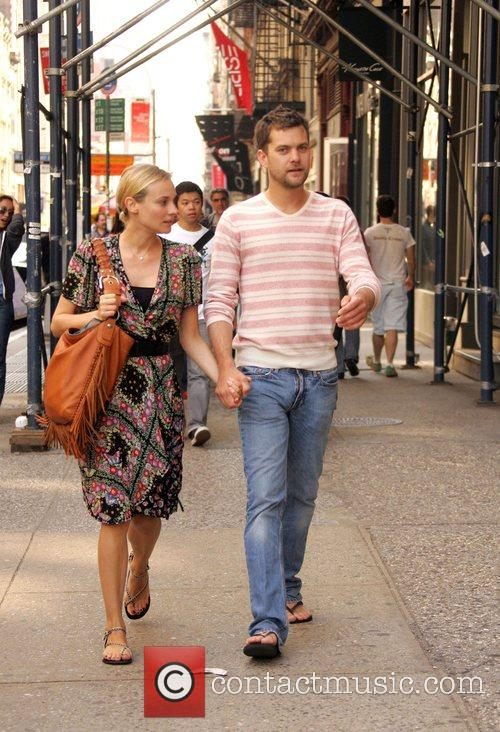 Hold hands as they walk through SoHo together