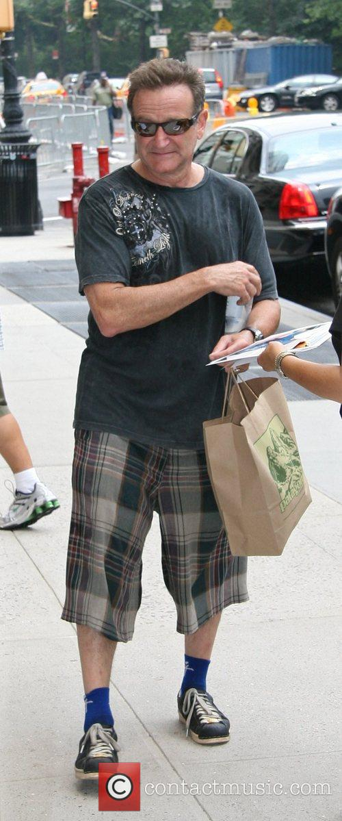 Robin Williams arrives at his Manhattan hotel carrying...