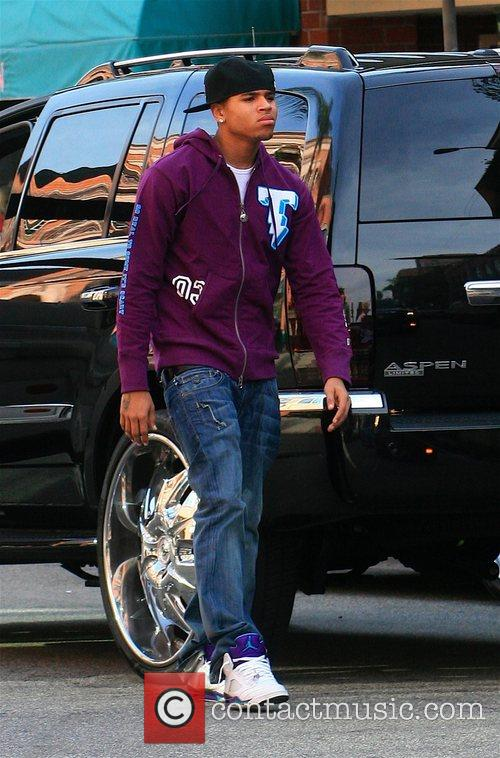 Chris Brown looks tense as he gets out...