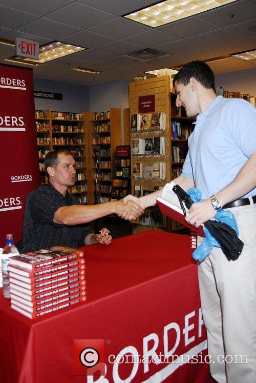 The Philadelphia Phillies catcher Chris Coste signs his...