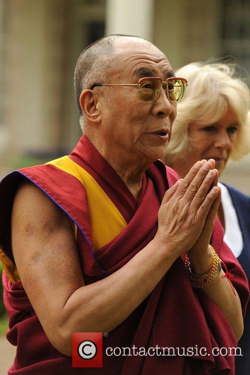 The Dalai Lama prays as he plants a...