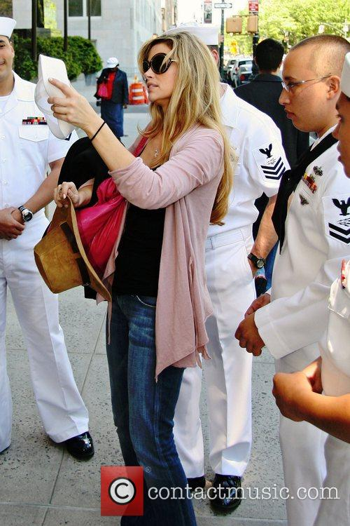 Denise Richards poses with servicemen, who are in...