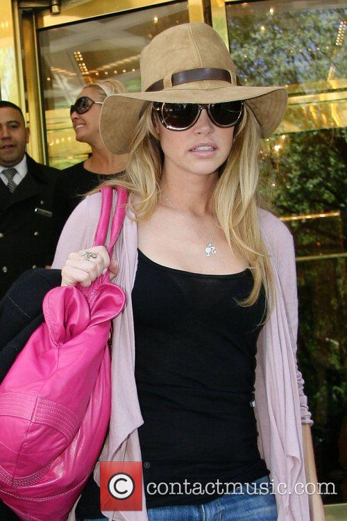 Denise Richards checks her luggage as she checks...