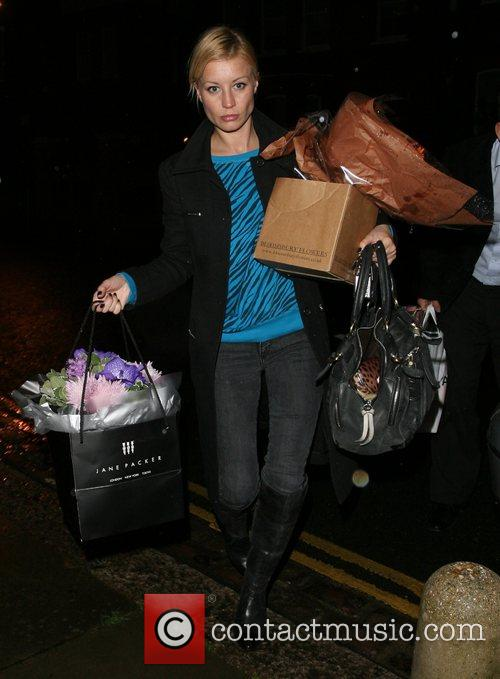 Denise Van Outen arrives home alone, weighed down...