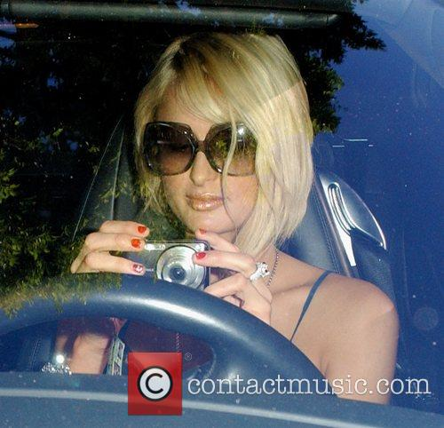 Paris Hilton taking pictures while arriving at Forte...