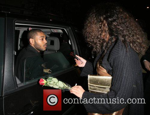 Kano gives a rose to a woman in...