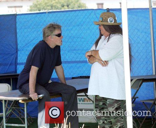 Gary Busey cahtting to a friend at the...