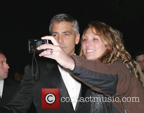 George Clooney poses with a fan outside Dan...