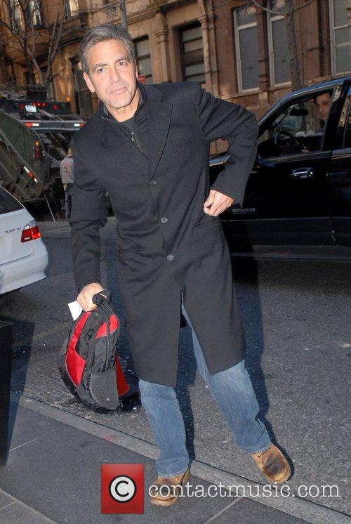 George Clooney holding a small rucksack and walking...