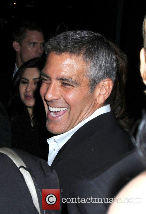 George Clooney signs for fans after leaving his...