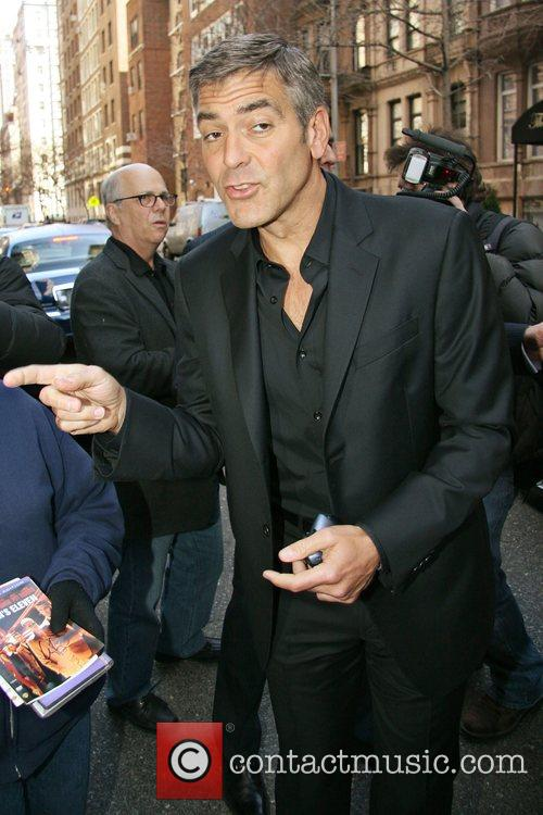 George Clooney signs autographs while leaving his Manhattan...
