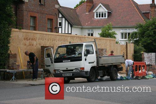Geri Halliwell has workmen building a brick wall...