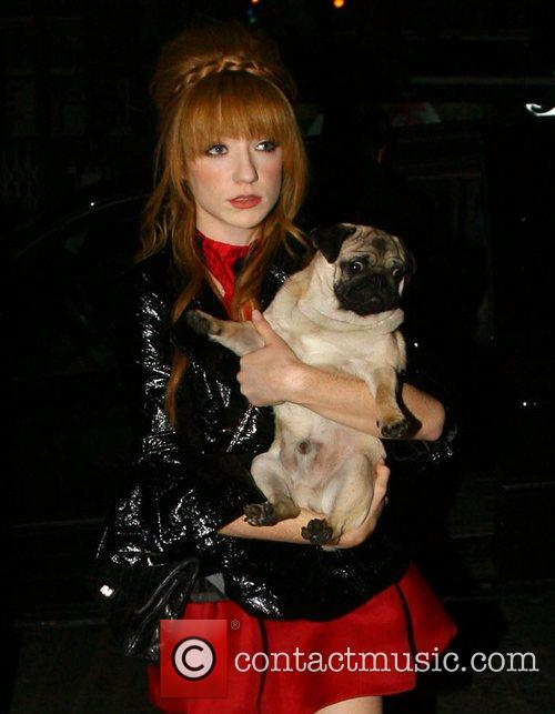 Carrying her pet Pug dog 'Elvis' when leaving...
