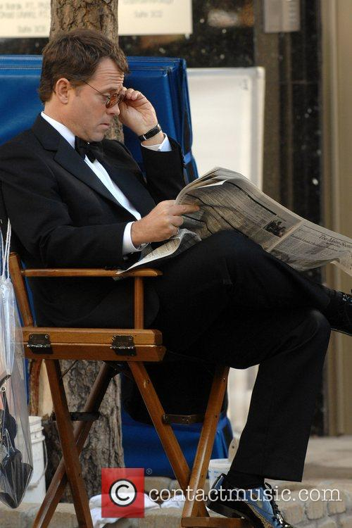 Greg Kinnear reading the New York Times during...