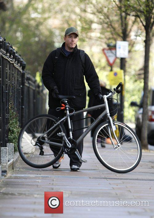 Guy Ritchie leaving home today on his bike