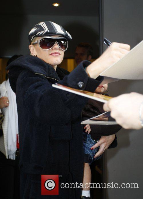 Gwen Stefani cradles her son Kingston whilst signing...