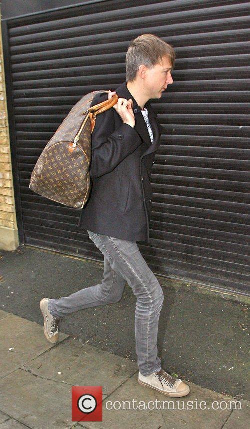 Jefferson Hack, clutches a Louis Vuitton bag while...