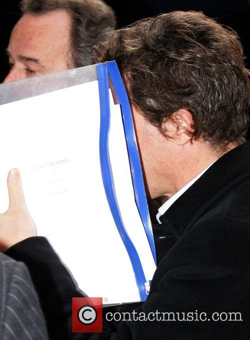 Hugh Grant covers his face with a script...