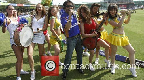 Indian singer Mika, center, performs with cheerleaders at...