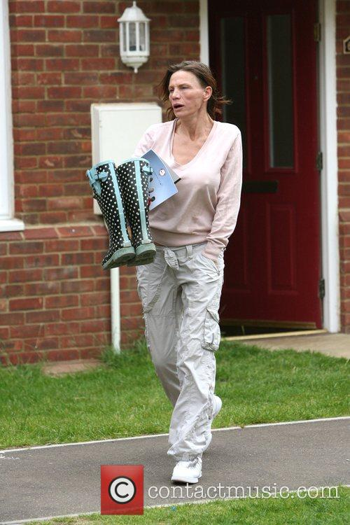 Jackie Budden carrying a pair of wellington boots...