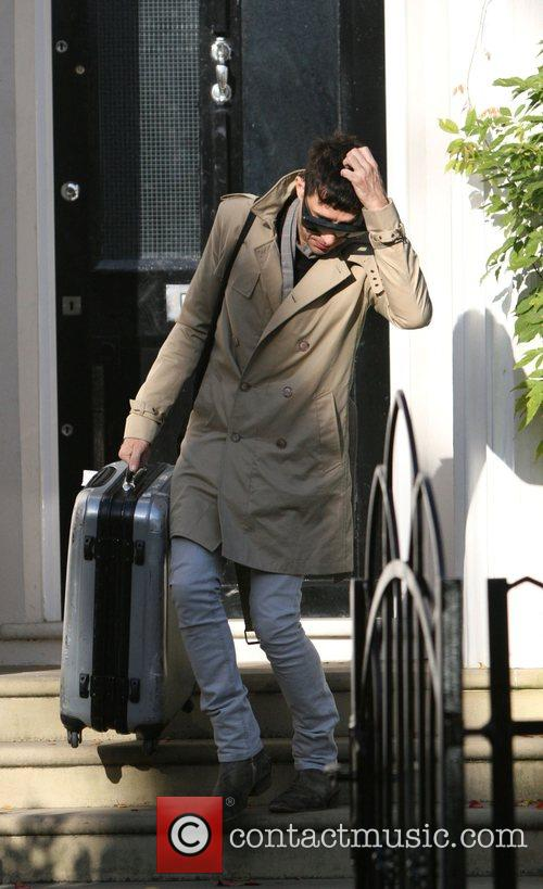 Leaving Davinia Taylor's house carrying a suitcase.