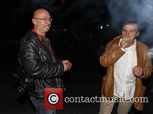 Neil Jordan smoking with a paparazzo outside restaurant...