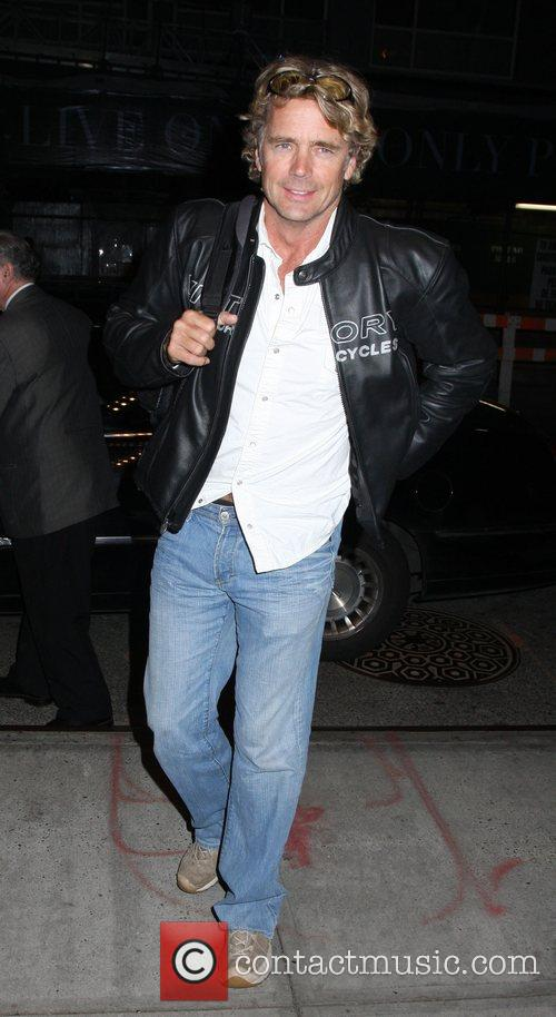 Arriving at a Soho hotel carrying his guitar