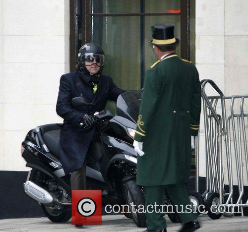 Leaving the Dorchester Hotel on his three-wheeler scooter
