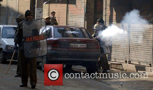 Indian policemen uses tear gas as Kashmiri protesters...